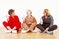 Senior women exercise class. Three smiling senior women with water socializing in a row in an exercise class stock photo