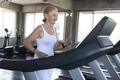 Senior women exercise jogging at gym fitness smiling and happy. elderly healthy lifestyle. Senior woman exercise jogging at gym fitness smiling and happy royalty free stock photos