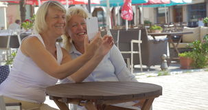 Senior women friends taking selfie in street cafe. Two happy senior women making mobile selfie sitting in outdoor cafe on bright summer day stock video
