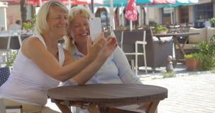 Senior women friends taking selfie in street cafe stock video