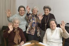 Senior women at the game table. Group of happy senior women playing mah-jong with friends waving hello Stock Image