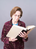 Senior Women With Glasses Reading A Book. A mature adult woman reading a large book Royalty Free Stock Photography