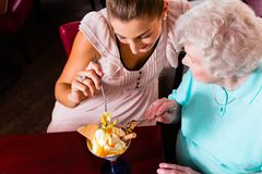 Grandmother and young woman eating ice cream Stock Images