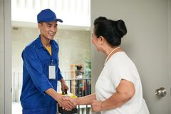 Greeting service man. Senior women greeting cheerful technician in her home royalty free stock photos