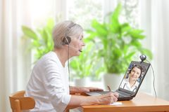 Senior woman doctor video call. Senior women in her living room in front of a laptop making notes during a video call with her female doctor Stock Photos