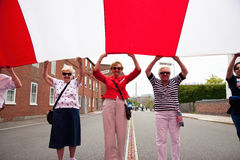 Senior women hold giant US Flag Stock Photo