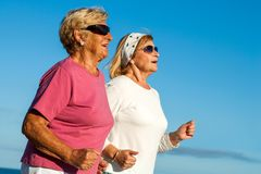 Senior women jogging. Close up portrait of two elderly women jogging outdoors royalty free stock photography
