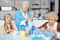 Senior women knitting warm clothes. Three pretty elderly women gathered together in living room and knitting warm clothes for their families with enthusiasm Stock Photos