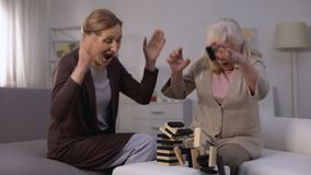 Senior women laughing playing block game and breaking tower, happy retirement stock video