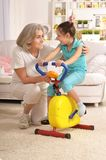 Senior woman and little granddaughter doing exercise Stock Image