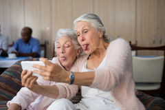 Senior women making face while taking selfie Stock Images