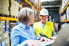 Senior woman manager and man worker working in a warehouse. Senior women manager and a men worker with barcode scanner working together in a warehouse Royalty Free Stock Photo