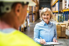 Senior woman manager and man worker working in a warehouse. Senior women manager and a men worker working together in a warehouse Royalty Free Stock Photos