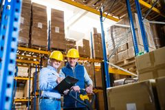 Senior woman manager and man worker working in a warehouse. Senior women manager and a men worker working together in a warehouse Royalty Free Stock Images