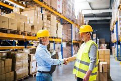Senior woman manager and man worker working in a warehouse. Senior women manager and a men worker working together in a warehouse, shaking hands Royalty Free Stock Images