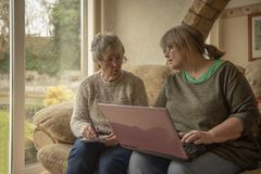 Senior woman and mature woman using a laptop. Senior women and mature women using a laptop in home setting royalty free stock image