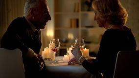 Senior woman and man flirting in restaurant, love feelings, aged couple romance royalty free stock image