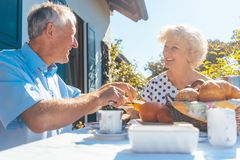 Senior woman and man having breakfast sitting in their garden Stock Images