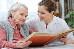 Nursing home. Senior women and nurse looking together at album with old photographs Royalty Free Stock Image