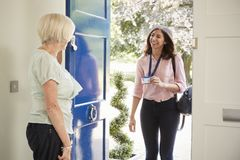 Senior woman opens door to female care worker showing her ID. Senior women opens door to female care worker showing her ID royalty free stock photos