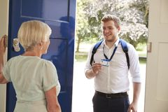Senior woman opens door to male care worker showing his ID. Senior women opens door to male care worker showing his ID stock photography