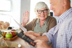 Financial calculations. Senior women with payment bill talking to her husband making financial calculations stock image