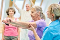 Senior woman doing exercise with elastic band. Senior women in physiotherapy is doing exercise with elastic band with the help of trainer royalty free stock image