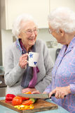 Senior women preparing meal together. Chatting and smiling Royalty Free Stock Image