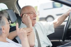 Senior woman protesting against husband driving and calling. Senior women protesting against her husband driving and calling stock image