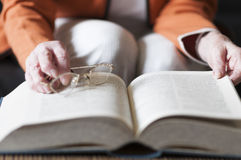 Senior women reading a book. Senior woman reading a book and in her hand she holds a pair of eyeglasses Stock Photo