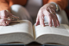 Senior women reading a book. Senior woman reading a book and in her hand she holds a pair of eyeglasses Royalty Free Stock Image
