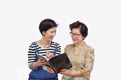 Senior woman reading a magazine with her daughter. Senior women reading a magazine with her daughter on white background royalty free stock photos