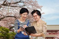 Senior woman reading a travel guidebook with her daughter. Senior women reading a travel guidebook with her daughter in Tokyo Japan stock photo