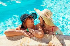 Senior woman relaxing with her adult daughter in hotel swimming pool. People enjoying vacation. Mother`s day stock photos