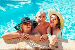 Senior woman relaxing with her adult daughter in hotel swimming pool. People enjoying vacation. Mother`s day stock image