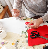 Senior women sews by hand. Senior woman sews by hand and making heart shape ornament Royalty Free Stock Photos
