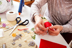 Senior women sews by hand. Senior woman sews by hand and making heart shape ornament Stock Images