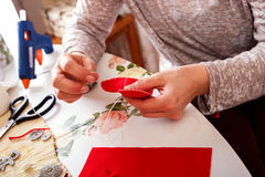 Senior women sews by hand. Senior woman sews by hand and making heart shape ornament Stock Photo