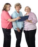 Senior Women Sing. Three senior women singing together from a songbook. On a white background royalty free stock photo