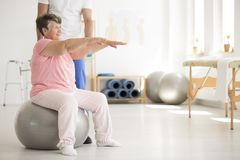 Senior woman maintaining balance. Senior women sitting on silver ball and maintaining balance during rehabilitation with physiotherapist stock images