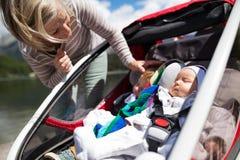 Senior woman and grandchildren in jogging stroller. Stock Photography