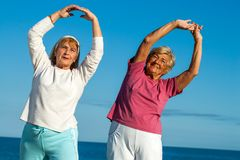 Senior women stretching arms outdoors. Stock Image