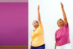 Senior women stretching in gym. Portrait of two Senior women doing aerobics in gym Royalty Free Stock Images
