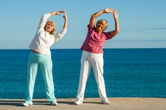 Senior women stretching at seafront. Stock Photos