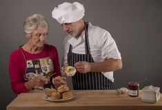 Senior woman taking cooking lessons with mature chef royalty free stock photography