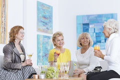 Senior women talking. Four elegant senior women sitting and talking over drinks Stock Photo