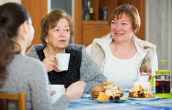 Senior women talking with girl while tea drinking Stock Photography