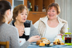Senior women talking with girl while tea drinking Royalty Free Stock Photo