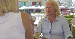 Senior women talking and having drinks in street cafe stock video footage