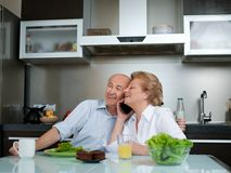 Senior woman talking on phone while man working in kitchen at home Royalty Free Stock Image
